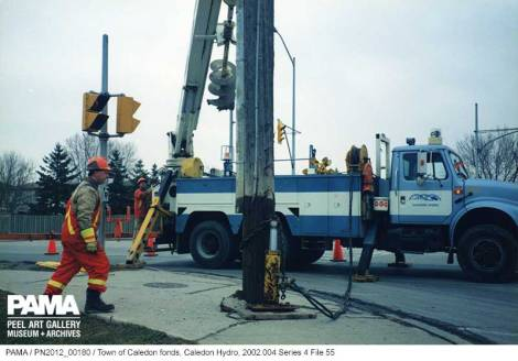 Hydro truck at intersection, hydro employees walk about.