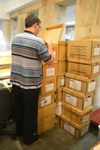 archivist looking through a pile of boxes