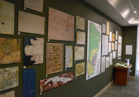 A series of maps on a green wall.